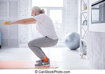 athlétique, personne agee, dumbbells, homme, s'accroupit