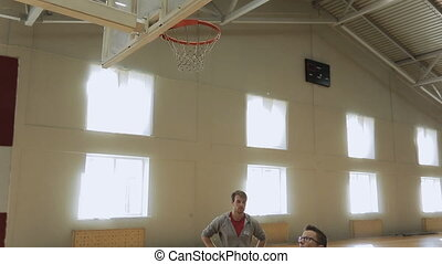 Athlet with instructor throwing heavy ball in basket. He...