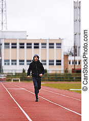 Athlete Asian young man running on racetrack in stadium. Healthy active lifestyle concept.