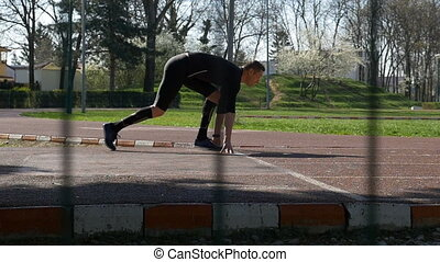 Athlete at starting line from block start position running on race track in the morning in slow motion