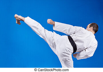 Athlete beats kicking leg - On a light background athlete...