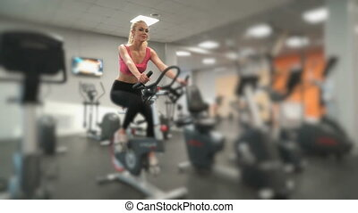 Athlete blonde engaged in the gym