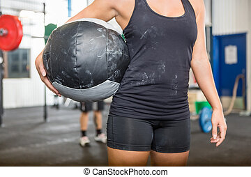 Athlete Carrying Medicine Ball At Gym - Midsection of female...