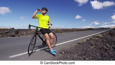 Athlete cyclist man drinking water after intensive cycling biking training, Healthy active lifestyle sports fitness man resting on bike after exercise. SLOW MOTION RED EPIC.