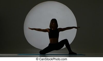 Athlete does the splits and tilts. Back light. Silhouette