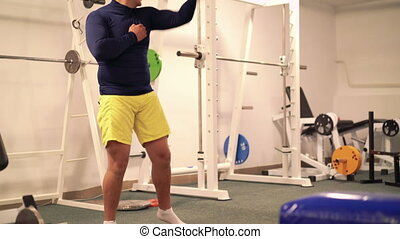 Athlete doing exercise for arms in the modern gym. 4k