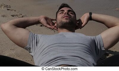 Athlete doing sit ups on the sand