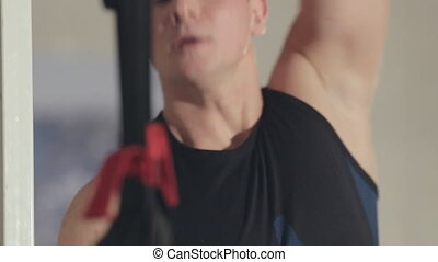 Athlete doing stretching of biceps muscle in gym