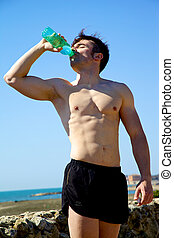 Athlete drinking water feeling thirsty after training -...