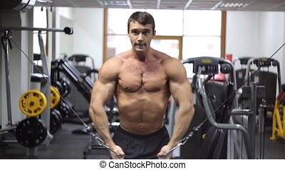 Athlete engage with crossfit in gym and looks straight. Crossover is mixing arms in a block training simulator. Isolated exercises for shaping pectoral muscles. It is well suited to athletes who base weight of pectoral muscles have been recruited and needs to be sanded. Target muscles when ...