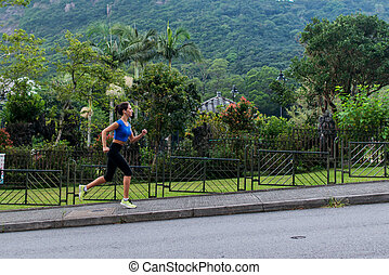 Athlete female runner doing cardio exercises in green mountainous area. Young woman jogging in nature landscape in summer