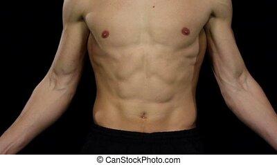 Athlete fulfills a sports training program. Close up. Slow motion. Black