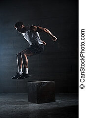 Athlete gave exercise. Jumping on the box. Phase touchdown. ...