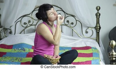 athlete girl eating donut on a bed with pleasure, forbidden...