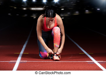 Athlete girl trying running shoes getting ready for race on track