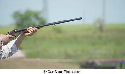 Athlete gunning from side-by-side shotgun training skeet...