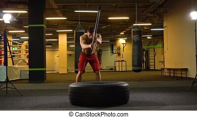 Athlete hitting tire with hammer - Young man in shorts...