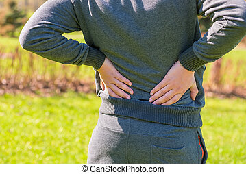 Athlete holding hands sore lower back