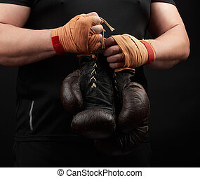 athlete in a black uniform holds very old brown boxing gloves in his hand