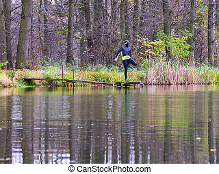 Athlete in black green  jacket stretching on lake mole or pier outside. Trail runner
