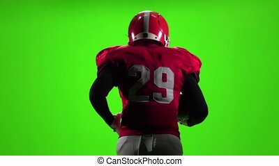 Athlete in gear runs with the ball. Slow motion. Green screen. Back view