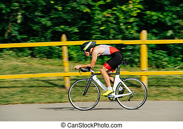 Athlete in low posture riding on a pro bike with streamlined helmet. Side view.