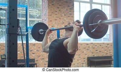 Athlete Lifting Barbell. Bodybuilder in the gym