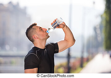 man drinking water from a bottle after jogging