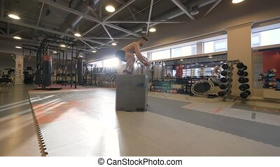 Athlete man jumping on platform on crossfit training in...