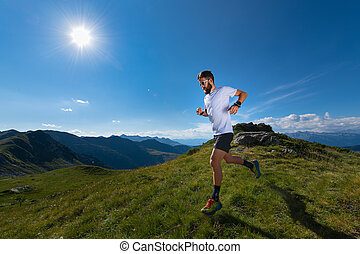 Athlete man practicing mountain running in the sun at high altitude