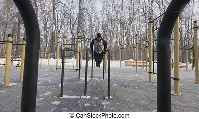 Athlete man training push ups exercise on bar on winter...