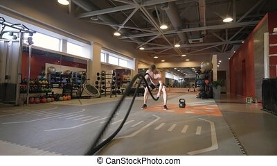 Athlete man training workout exercise with ropes in fitness...