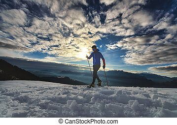 Athlete man trains with snowshoes at sunset in the mountains