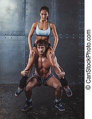 Athlete muscular sportsman doing exercising squats with woman sitting on his shoulders Crossfit fitness sport training lifestyle bodybuilding concept.