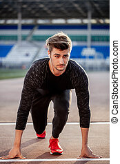 athlete on starting position at running track. Runner practicing run in stadium racetrack