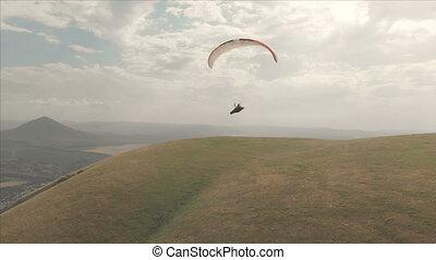 Athlete paraglider flies on his paraglider next to the...