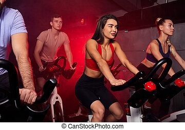 athlete people in gym, perfect shaped muscular people training on bicycle