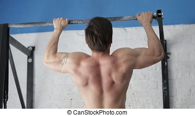 Athlete pulls up on horizontal bar. Muscular back gymnast