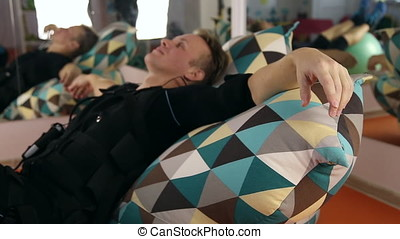 Athlete resting after ems training, he is lying on a large...