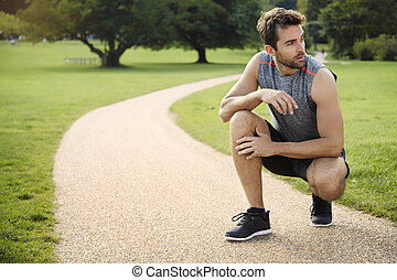 Athlete resting in park on path