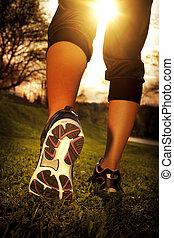 Athlete runner feet running on grass closeup on shoe. Woman fitness sunrise jog workout wellness concept.
