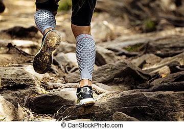athlete runner runs rocks in mountain. closeup of legs...