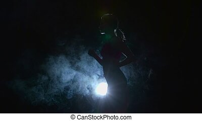 Athlete running lightly on a black background illuminated by...