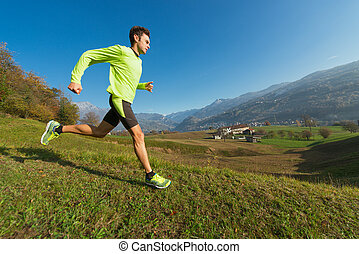 Athlete runs downhill in the meadow in a valley of the Italian Alps.