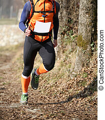 Athlete runs fast during the triathlon race on the mountain trai