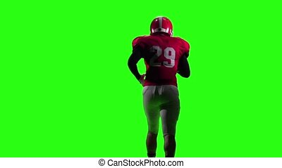 Athlete runs in a red helmet and protective gear with the ball in his hands. Green screen. Back view. Slow motion