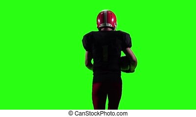 Athlete runs in a red helmet and protective gear with the ball in his hands. Green screen, back view, slow motion