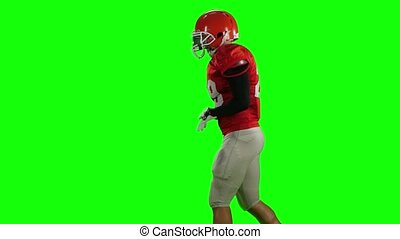 Athlete runs in protective gear with helmet and gloves. Green screen
