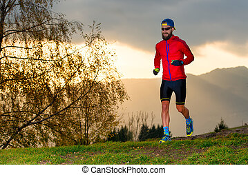 Athlete runs in the mountains at sunset