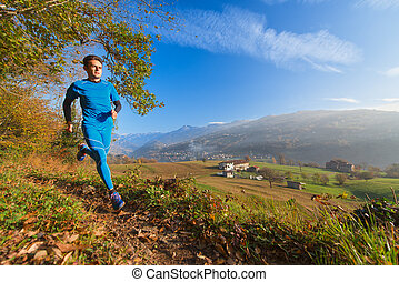 Athlete runs on mountain trail in a valley of the Italian Alps